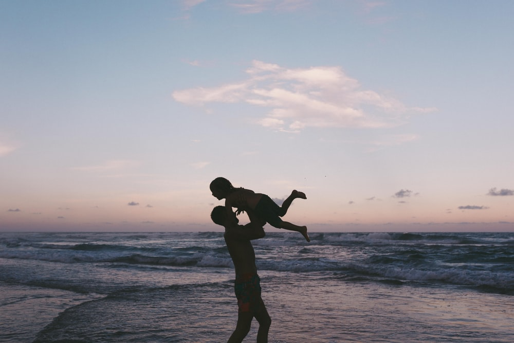 man carrying baby in seashore