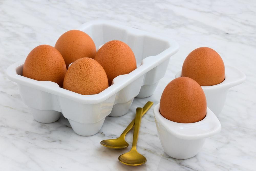 six brown eggs on white egg sorter