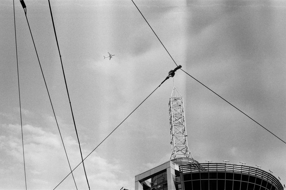 grayscale photography of airplane flying above building with tower