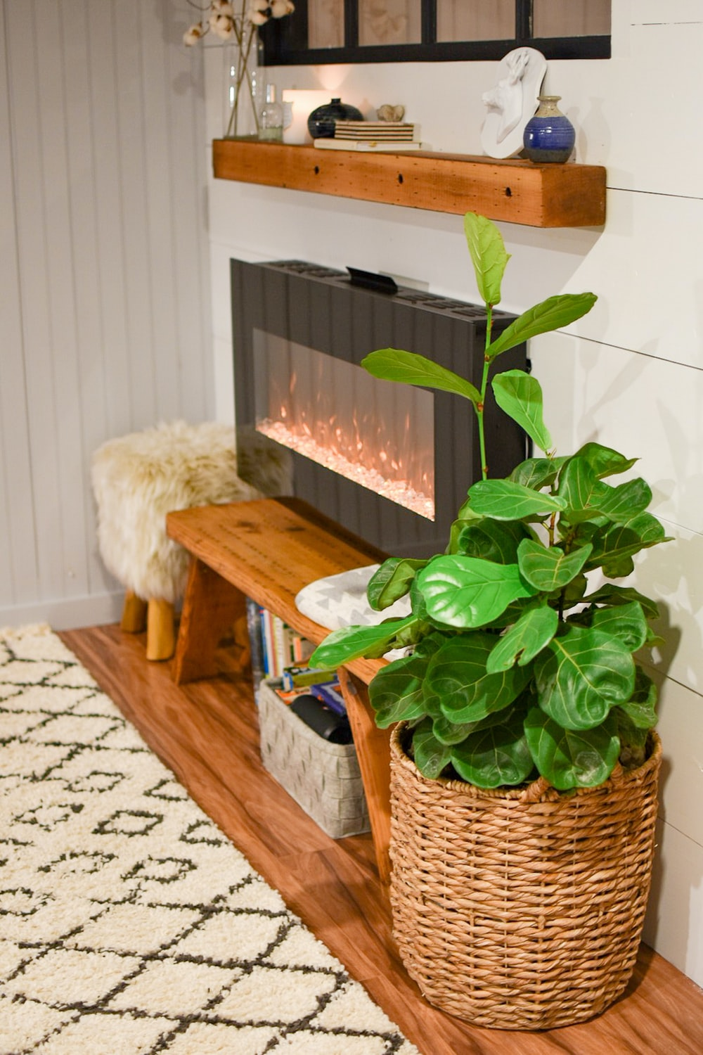 green-leafed plant on wicker basket besides gray electric fireplace