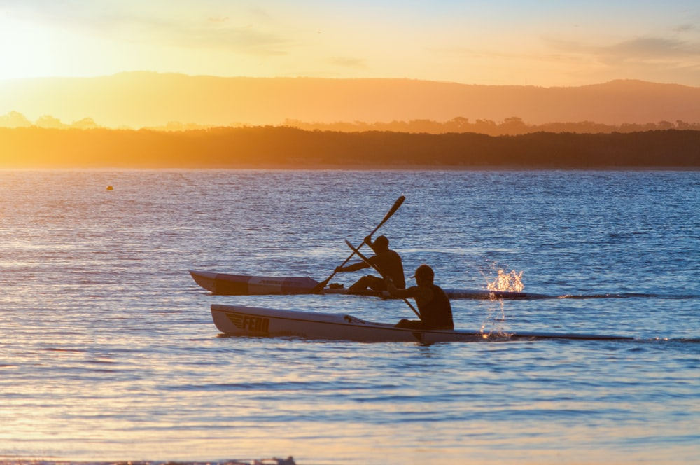 two men rowing canoes during golden hour