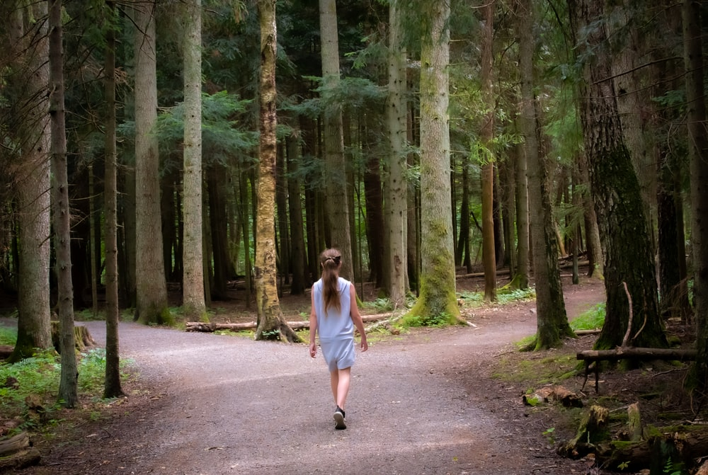 girl walking near trees