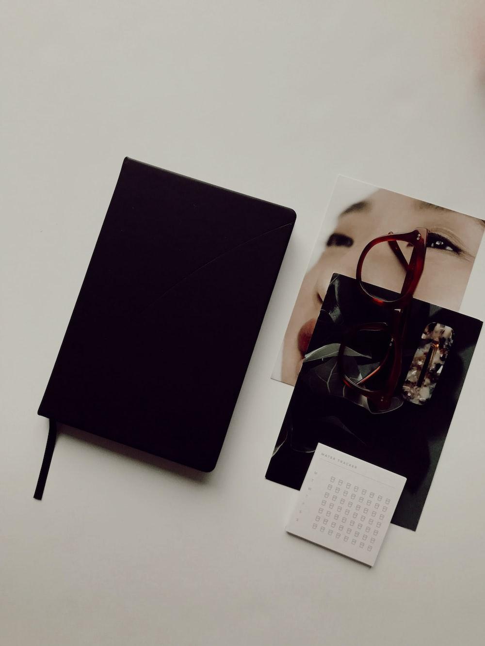 black book besides brown eyeglasses and photos