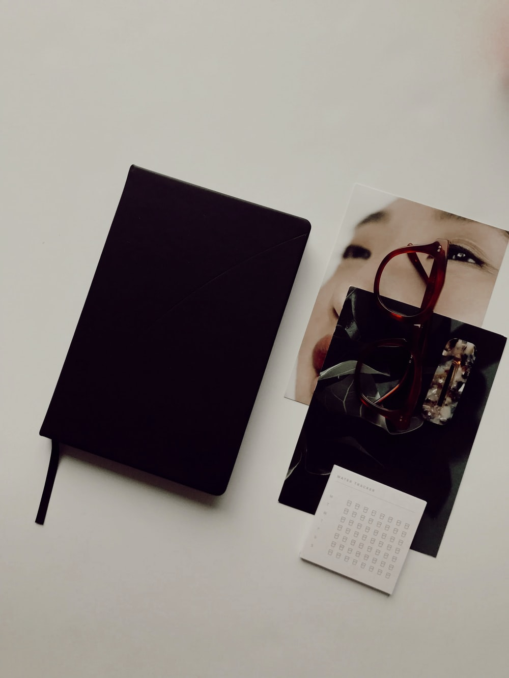 black book besides brown eyeglasses and photos