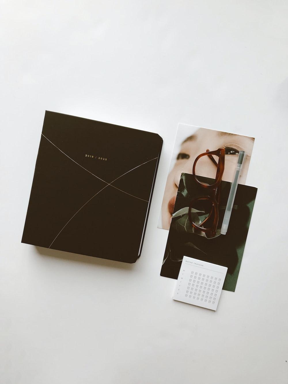 book beside eyeglasses on table