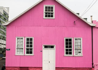pink wooden house showing closed white wooden door