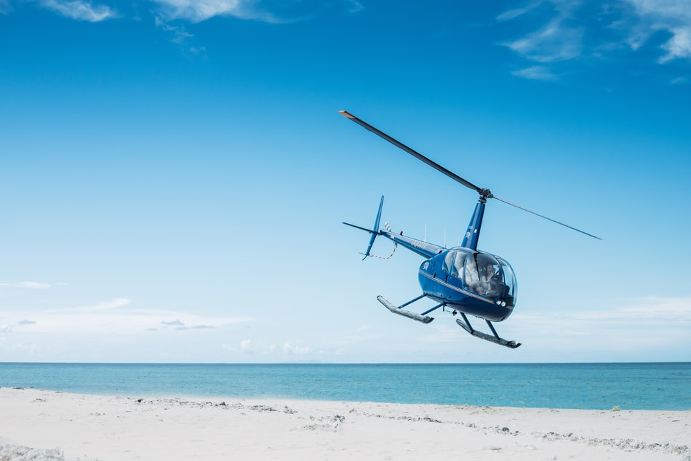 blue helicopter flying on beach