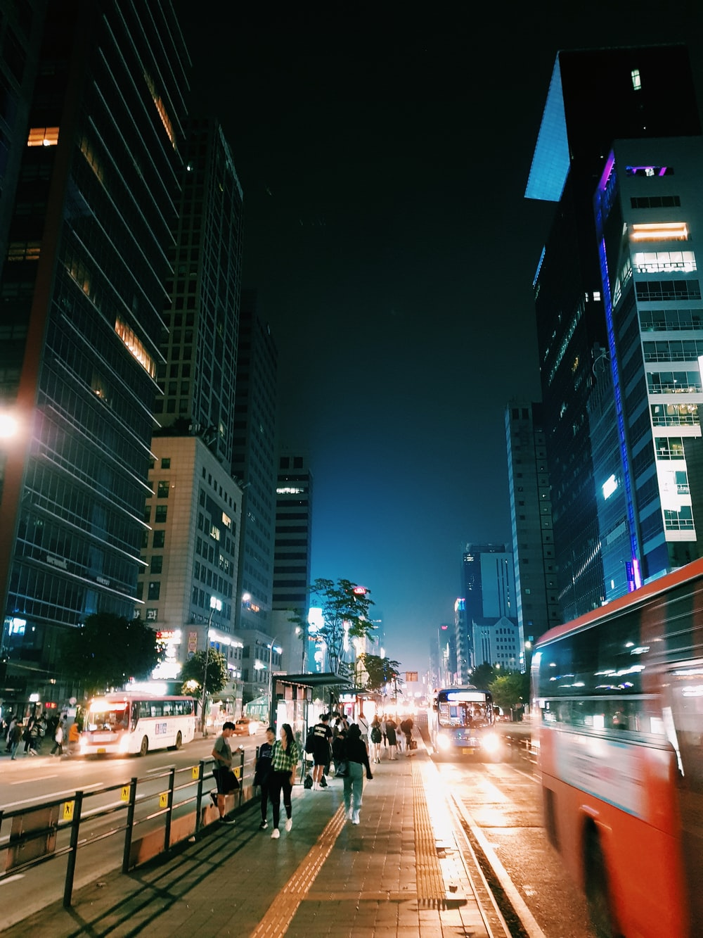 people walking on sidewalk during nighttime