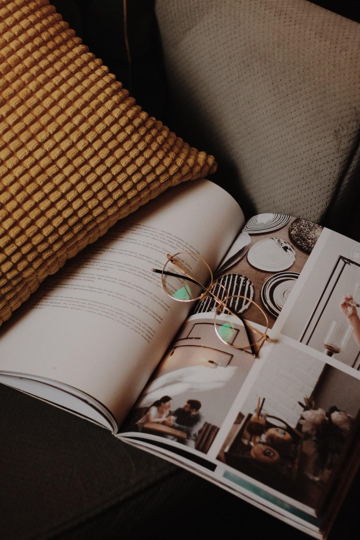 eyeglasses on magazine beside throw pillow on sofa