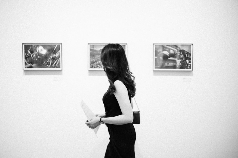 grayscale photo of woman walking near photos on wall