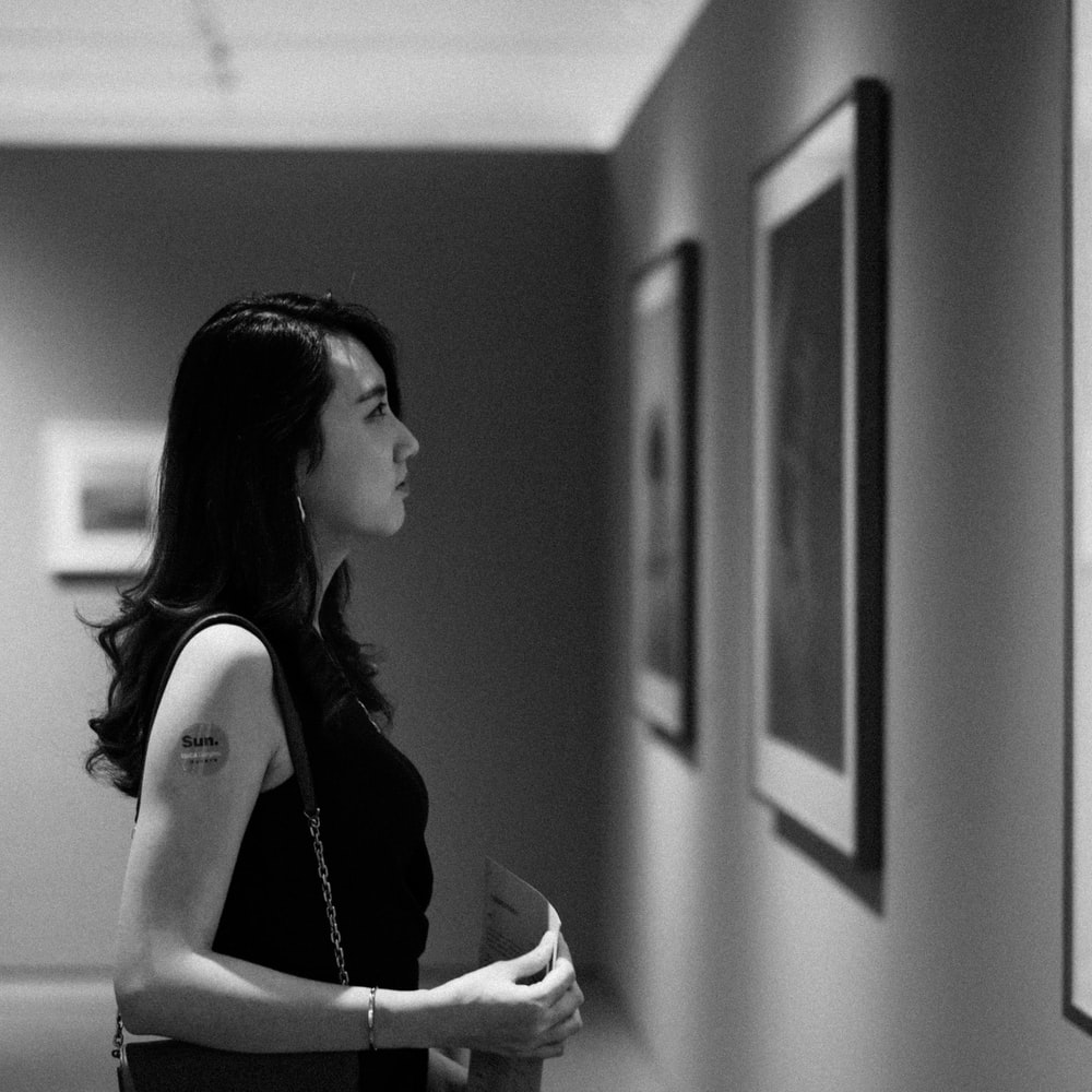 grayscale photo of woman facing painting