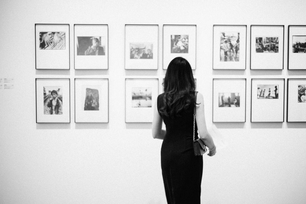 grayscale photo of woman watching photos on wall