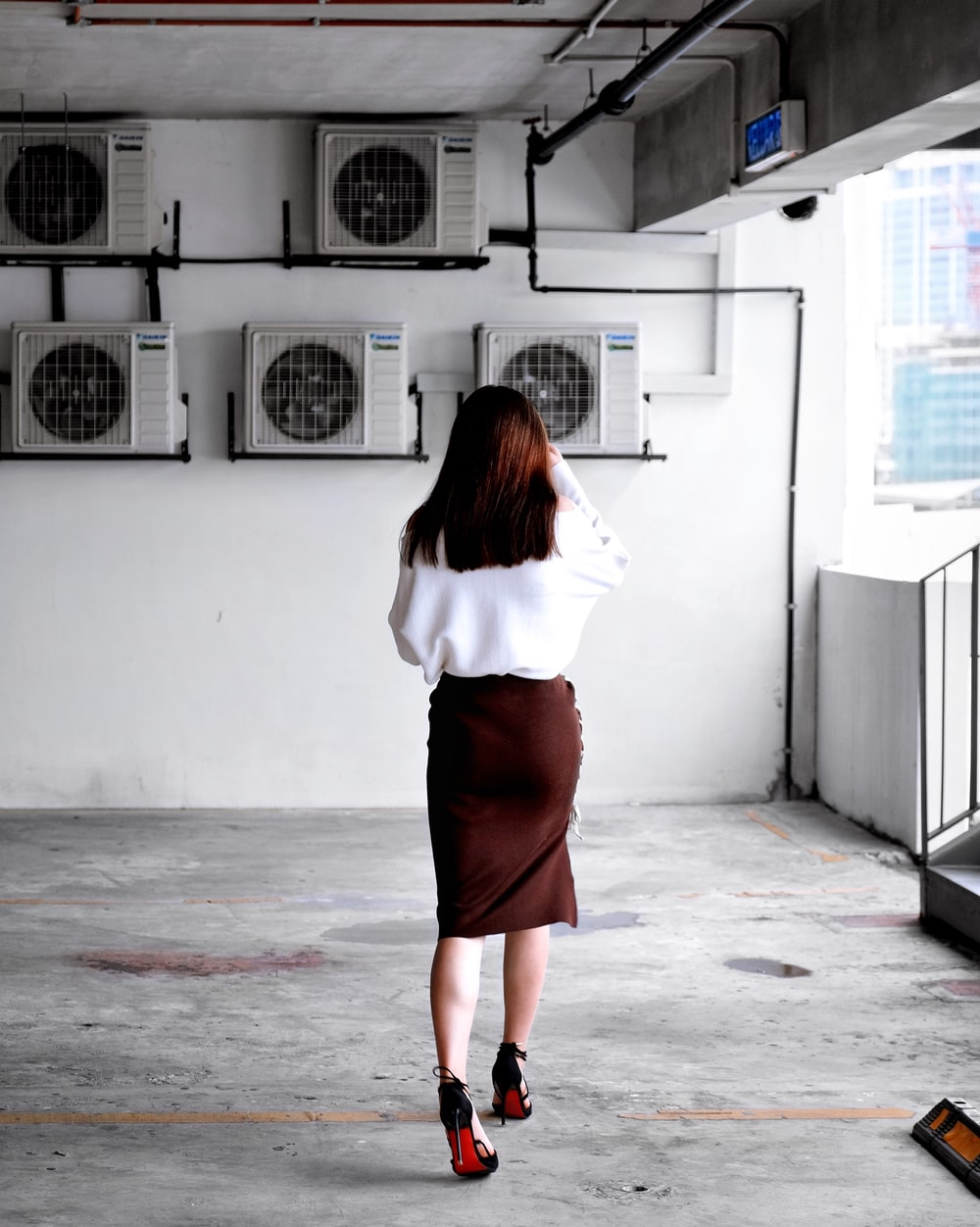 woman facing towards air condensers