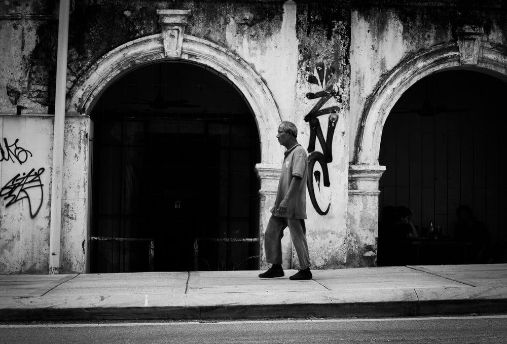 grayscale photography of man walking on pathway near building