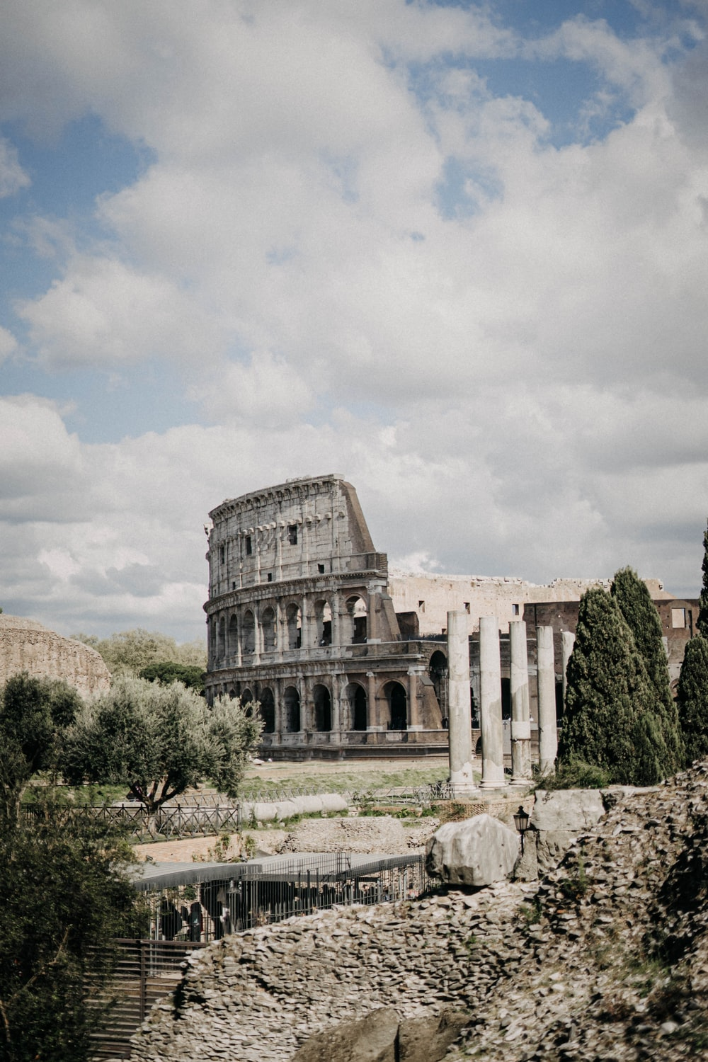 people standing near Colosseum in Rome, Italy under white and blue skies during daytime