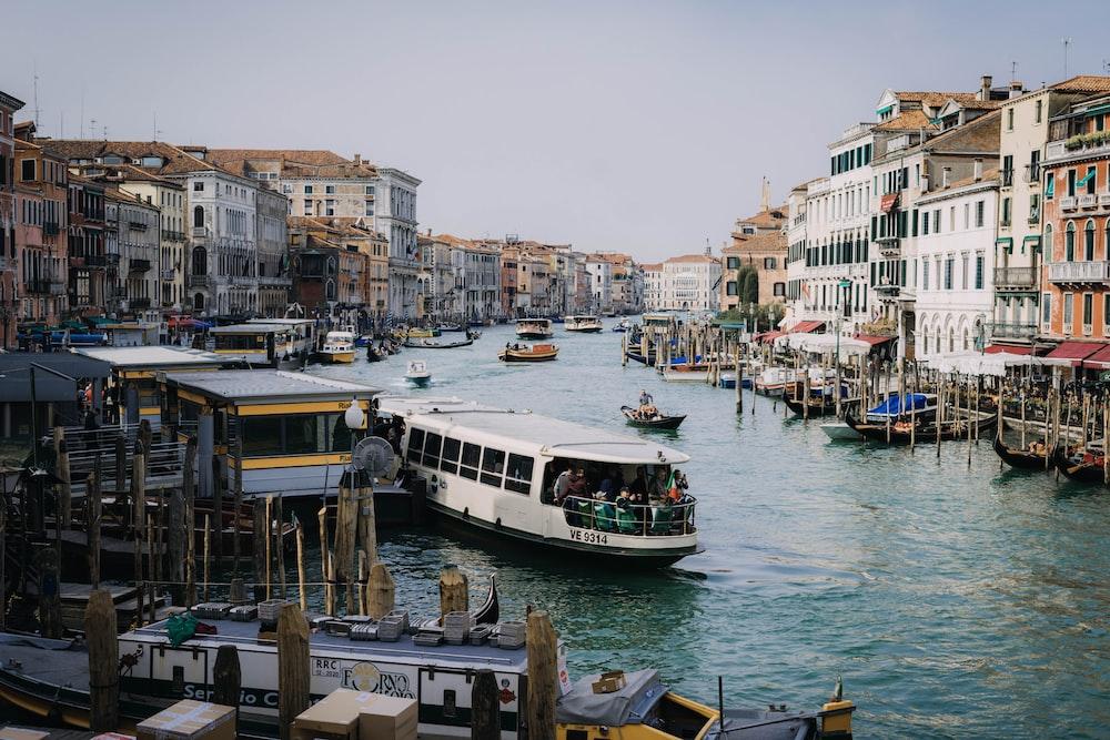 boats in body of water between buildings