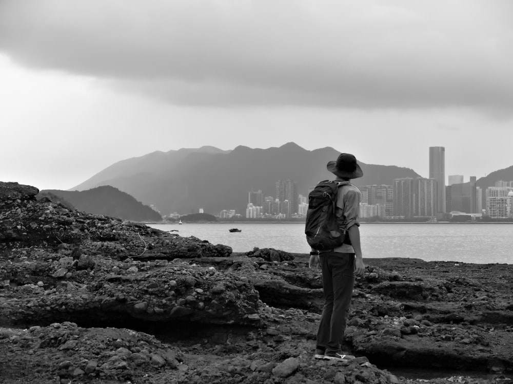 grayscale photography of man standing near sea viewing city with high-rise buildings