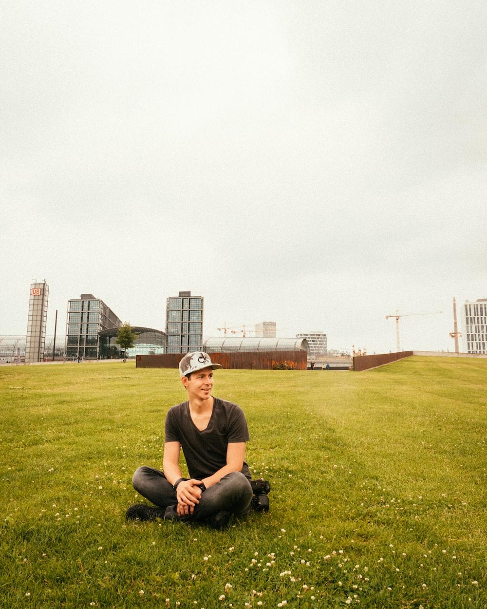 man wearing black crew-neck t-shirt sitting on grass during daytime