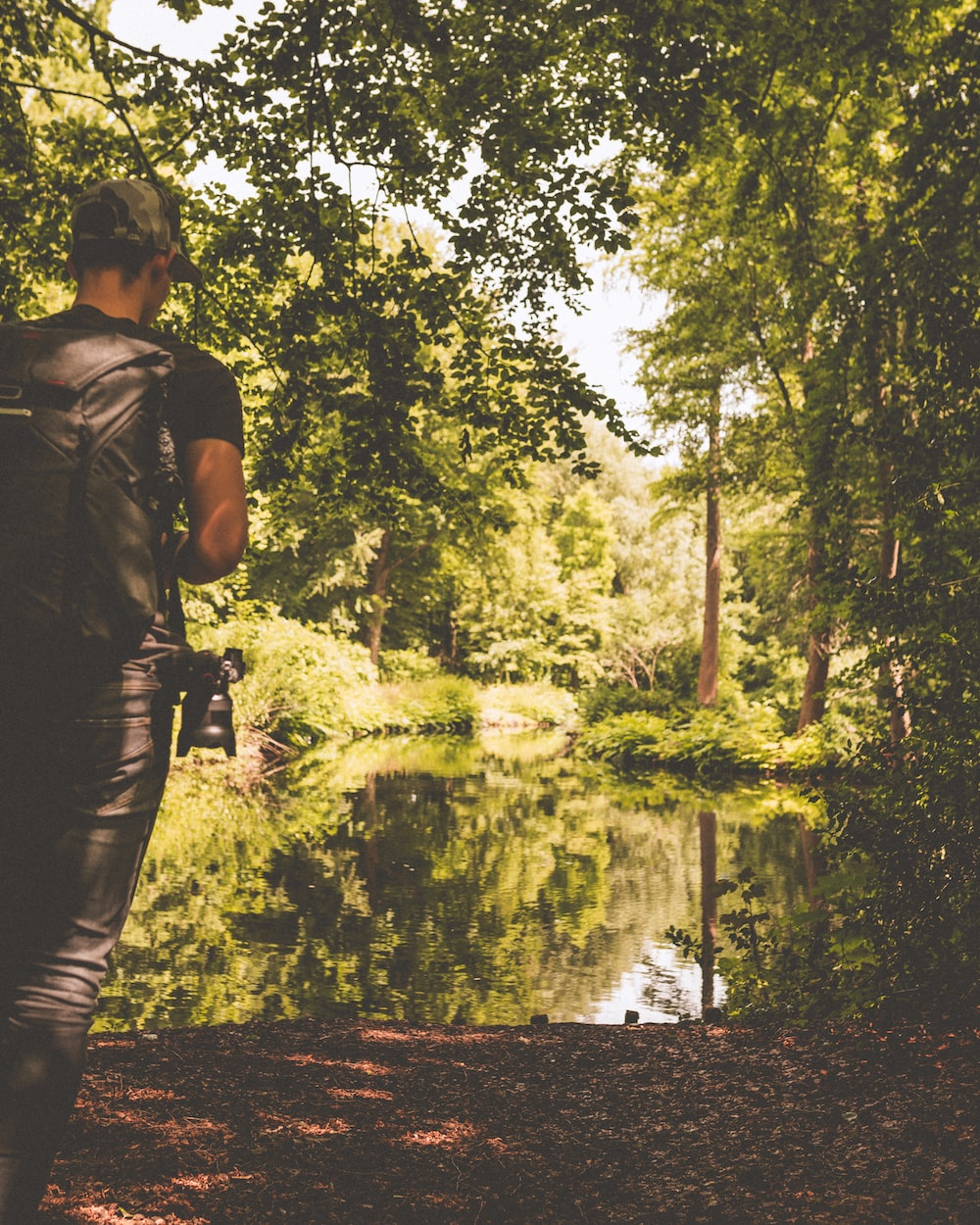 man standing near body of water surrounded by trees