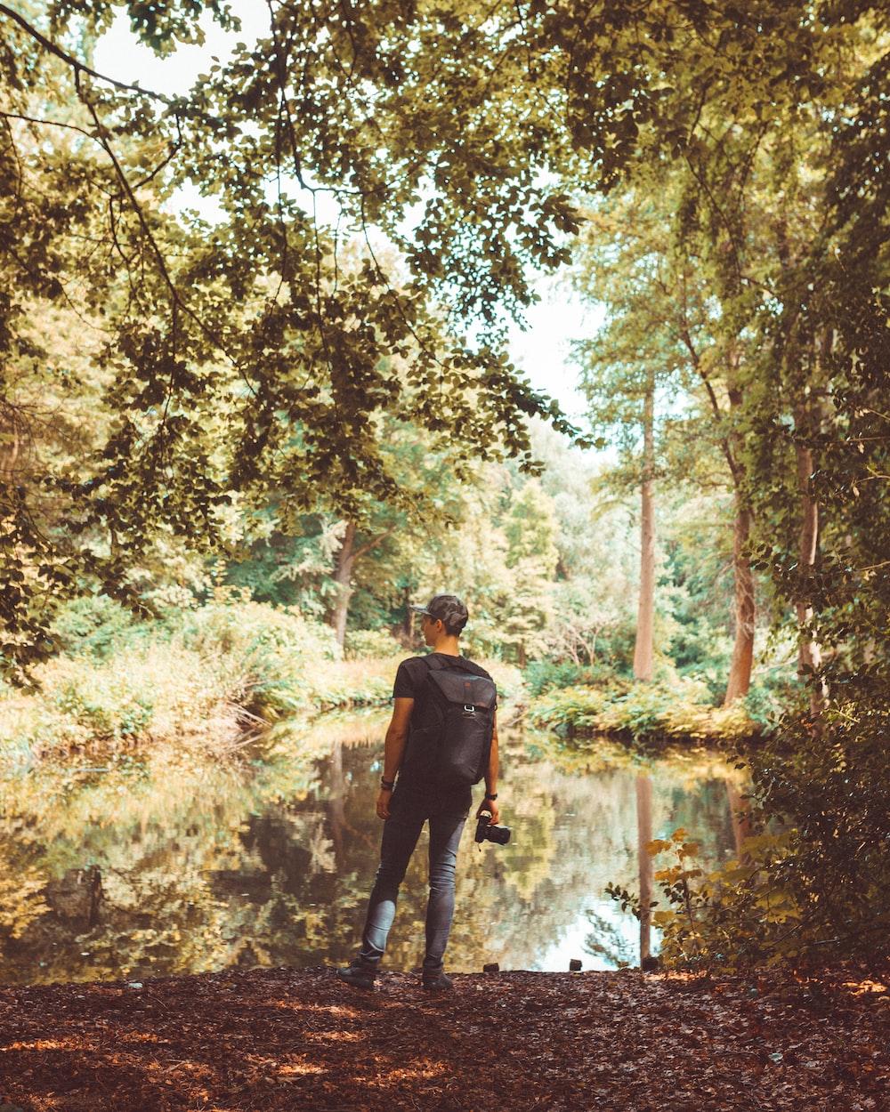 man standing near pond