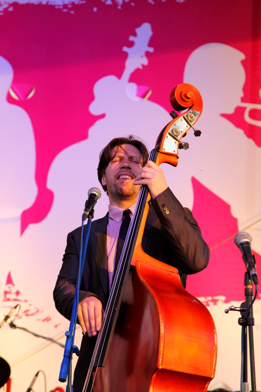 man playing cello in front of microphone
