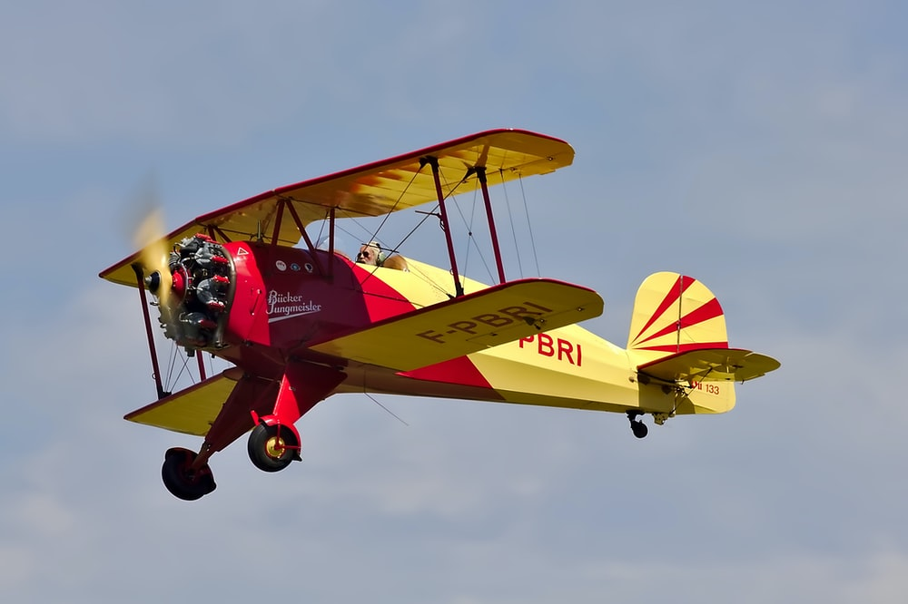 low angle photo of yellow and red biplane