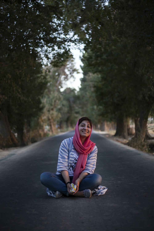 woman sitting on road between trees