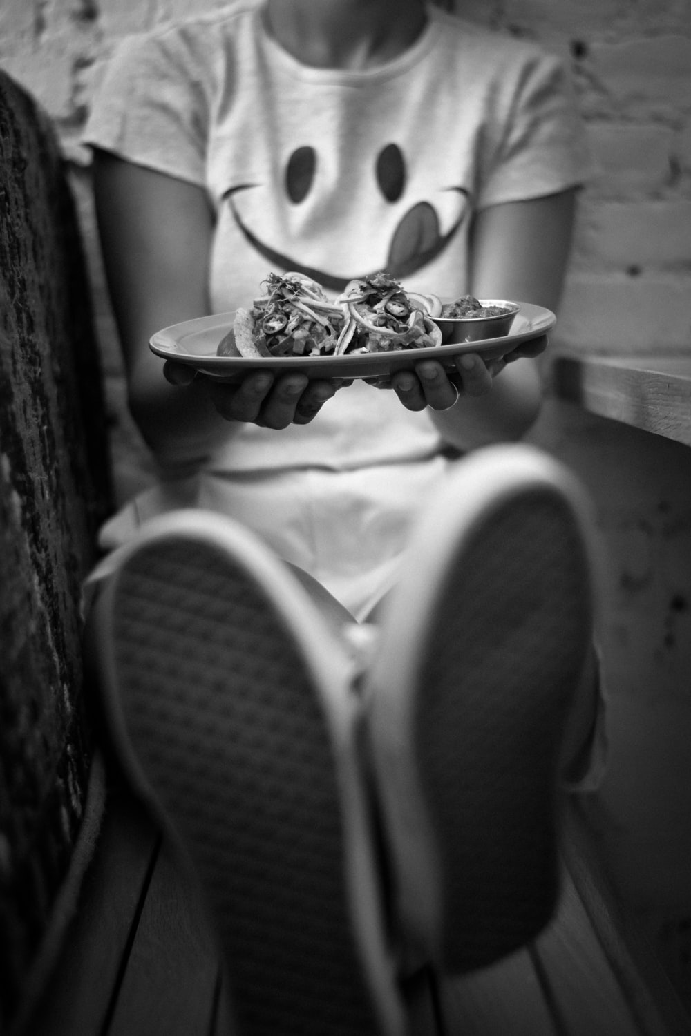 grayscale photography of woman holding plate with food while sitting and leaning near wall