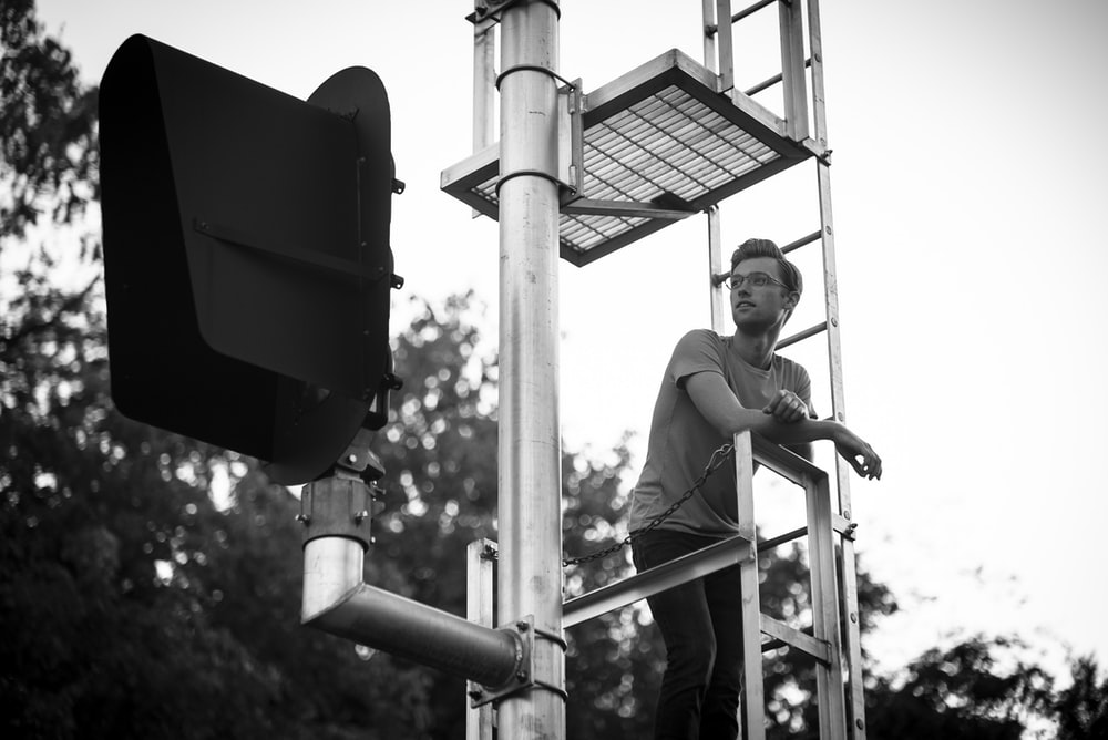 grayscale photography of man standing on tower
