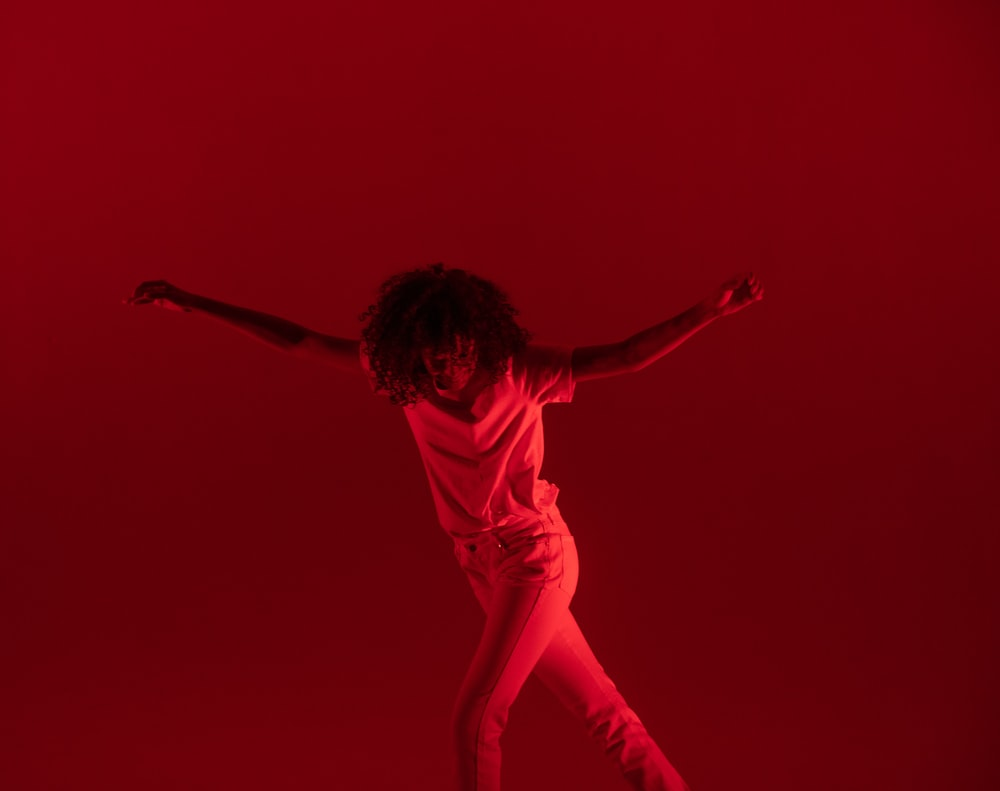 photography of woman dancing near red background