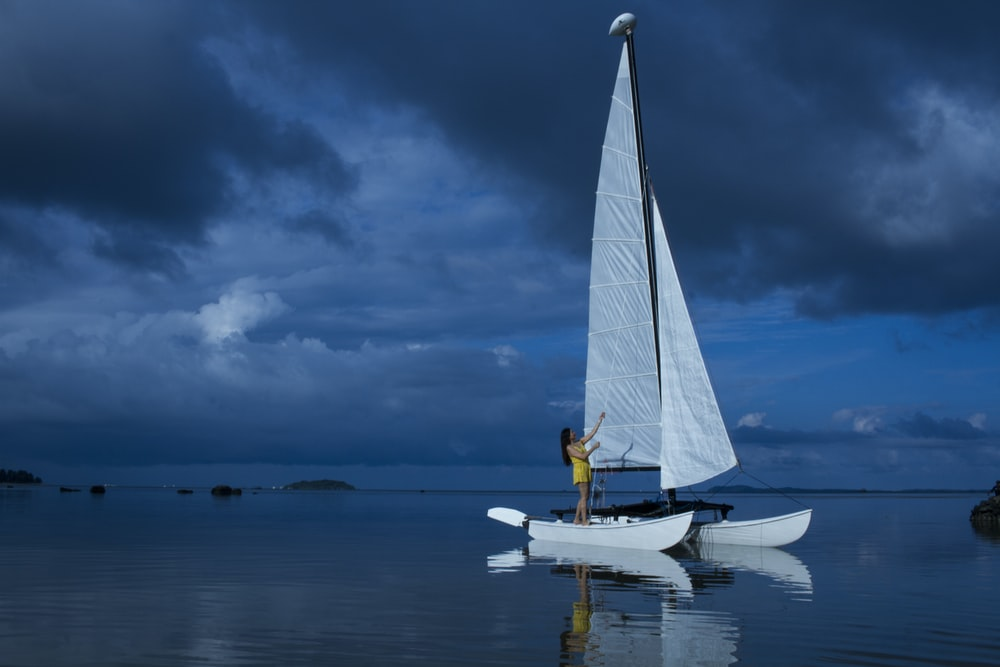 woman standing in white sailing boat on blue sea during night time