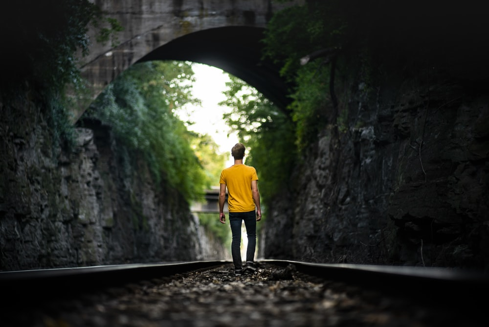 man walking on train track during day