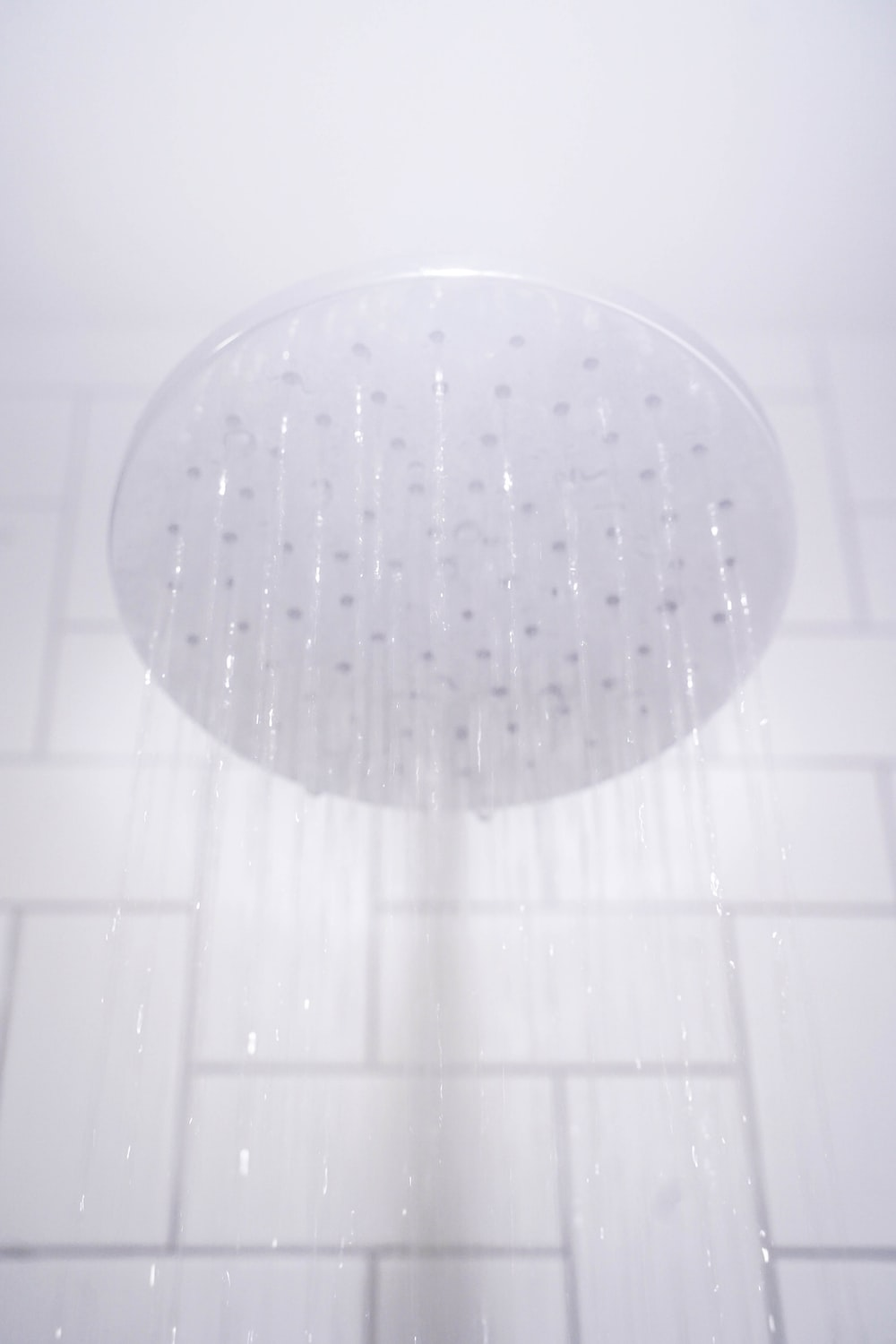 water from round gray stainless steel shower head