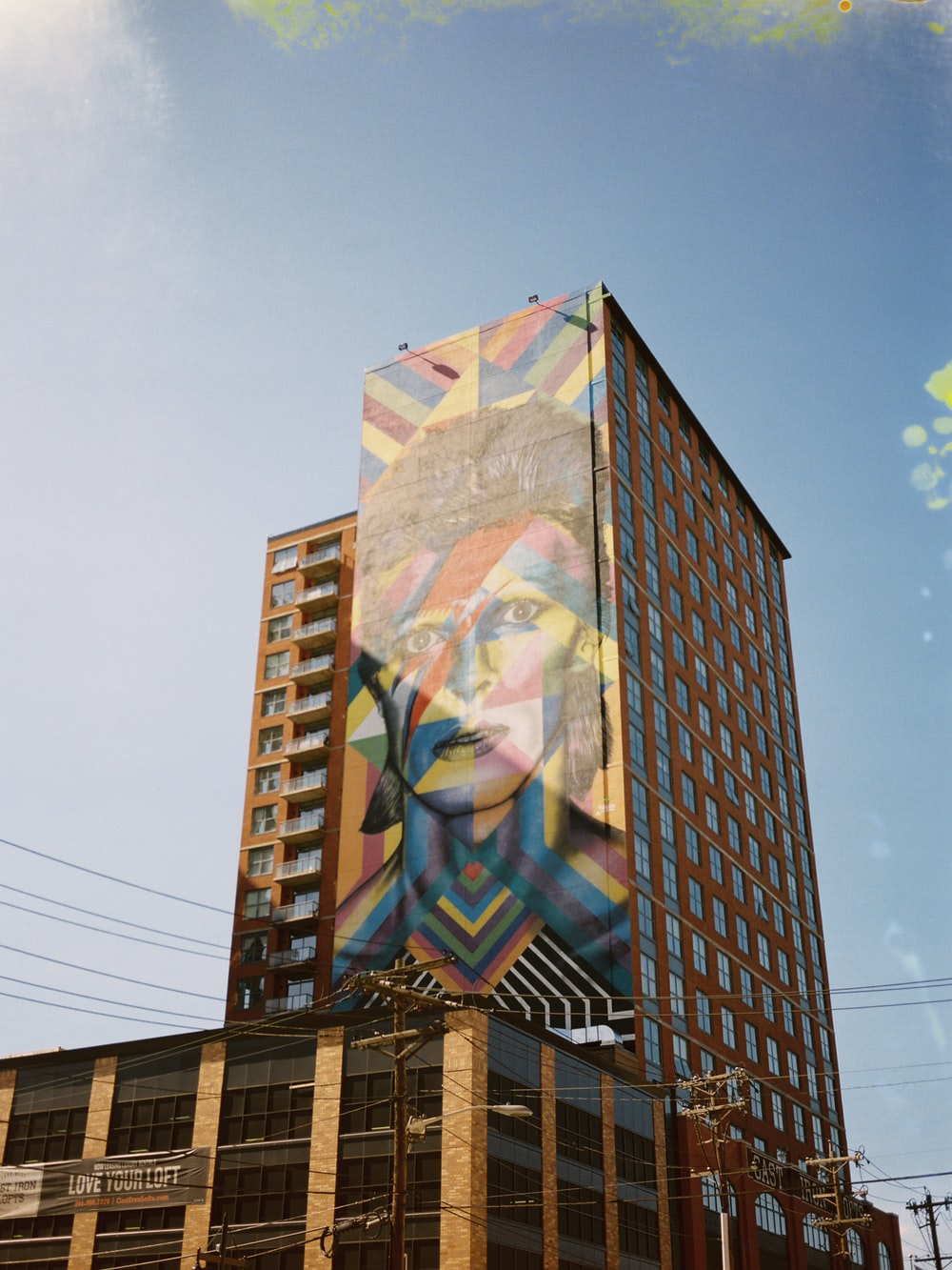 brown high-rise building with multicolored woman graphic painting under blue and white skies during daytime