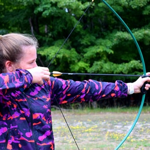 close-up photography of girl holding composite bow
