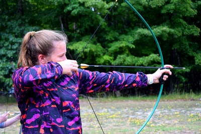 close-up photography of girl holding composite bow bow zoom background