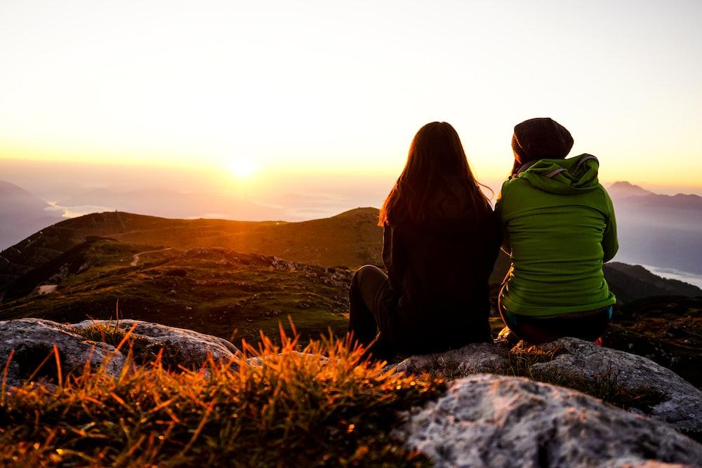 two women sitting on rock boulder