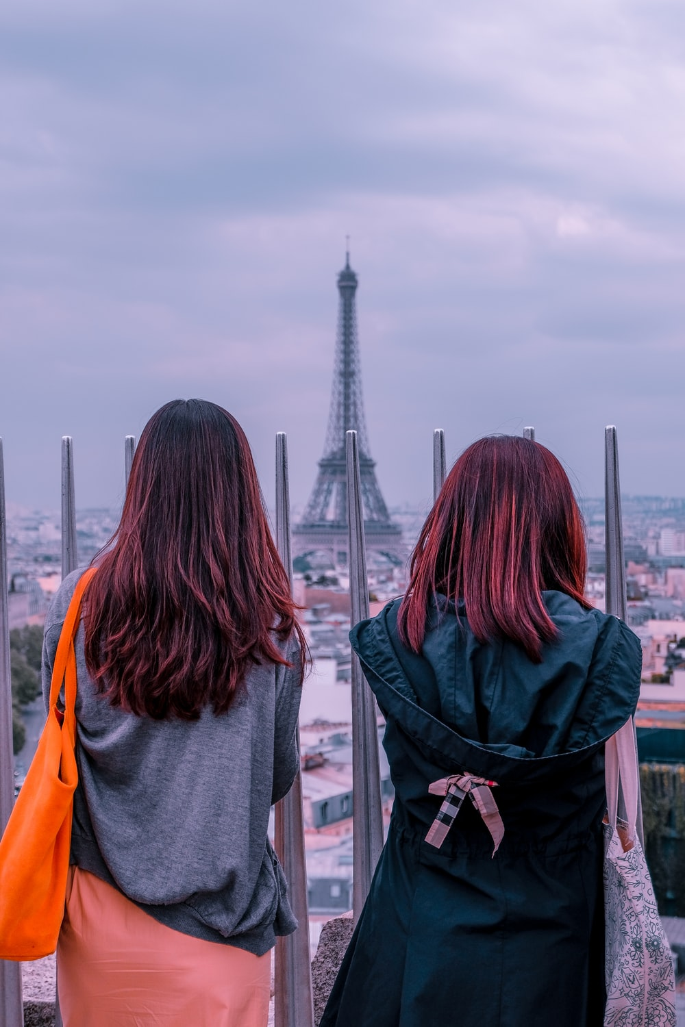 two woman standing near outdoor facing on Eiffel Tower during daytime