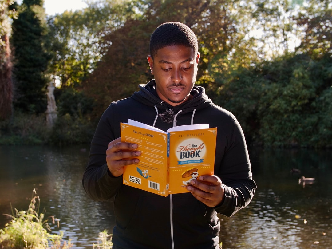 A man deep in thought. Reading maketh a full man...  Holding a copy of The Thought Book 2 by Jay Mullings