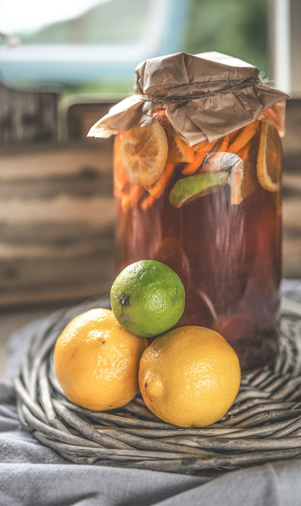 glass jar on gray surface beside lemons