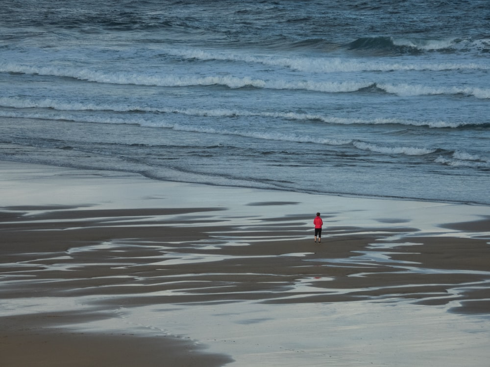 person wearing red shirt standing on seashore
