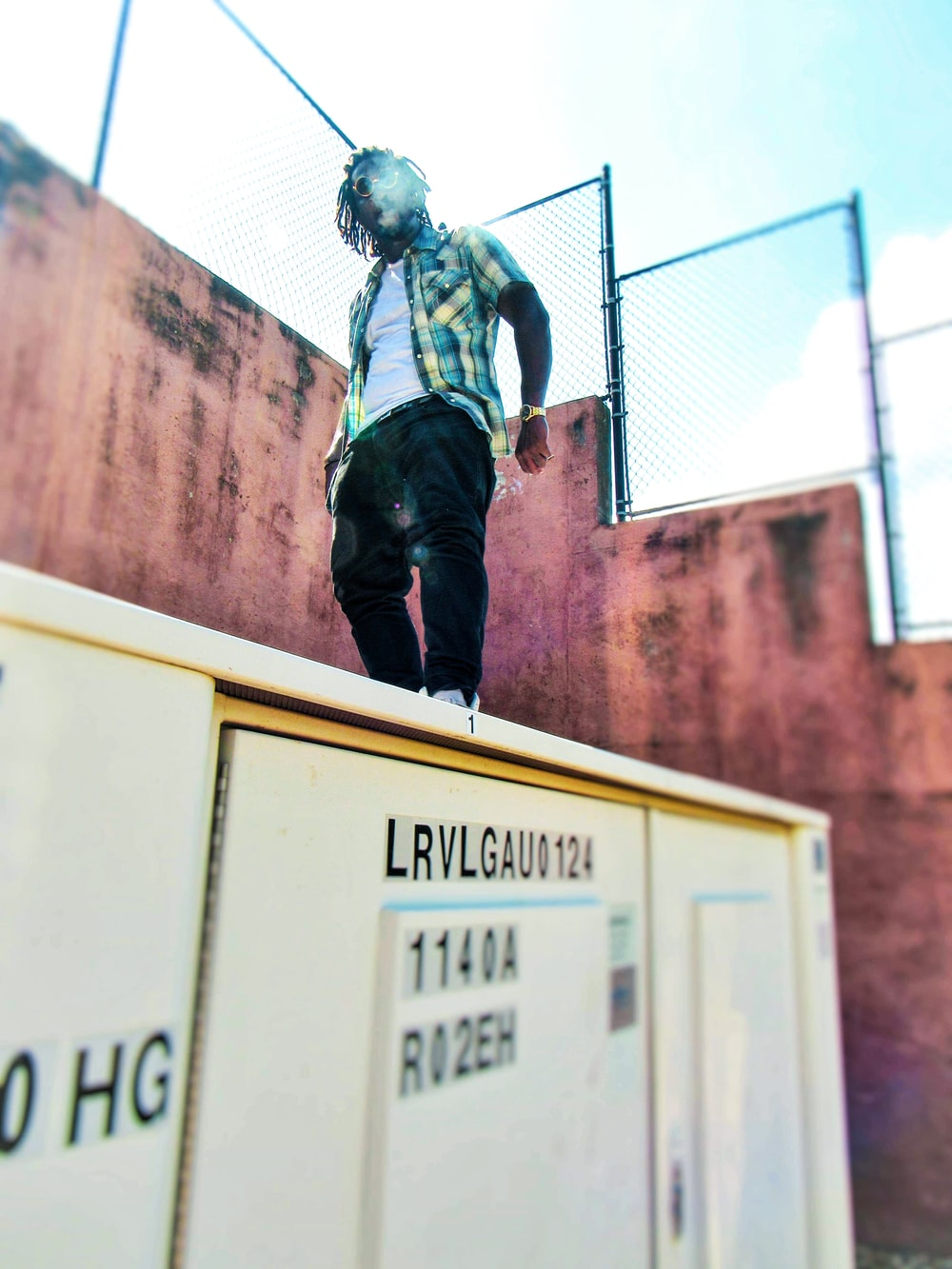 man standing on top of box during daytime