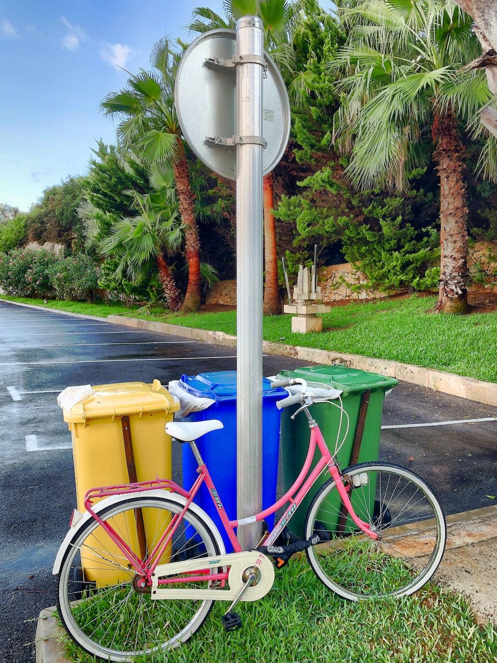 pink step-through bike parked beside garbage bins during daytime