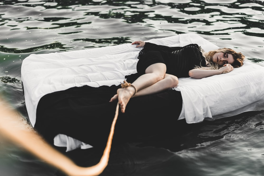 woman wearing black dress laying on bed