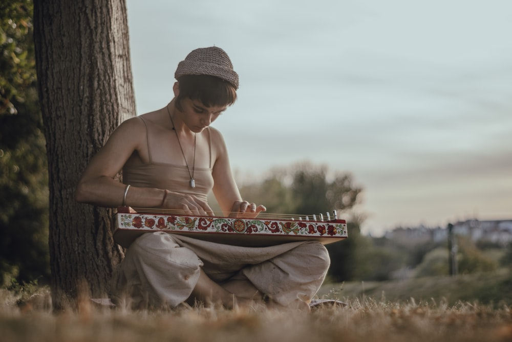 woman wearing beige blouse and pants sititng on brown grass field bihind of tree bark while playing musical instrument