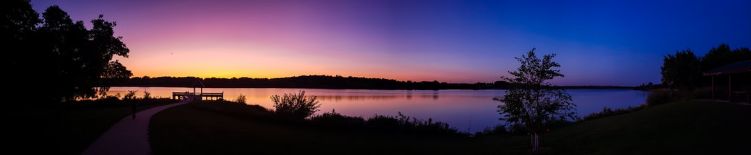 Panorama of a lake during rainbow-colored sundown.