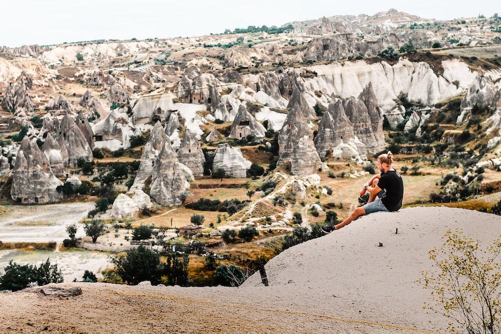 man sitting on rock formation