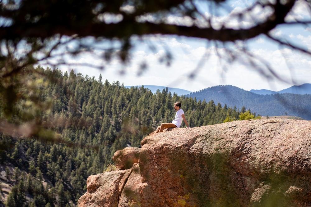 man sitting near rock cliff
