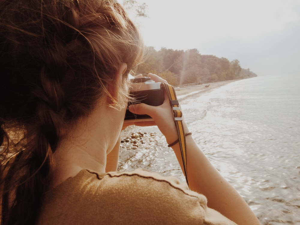 woman taking picture of shore and trees