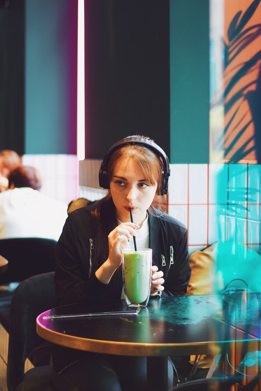 woman sitting and sipping beverage from straw